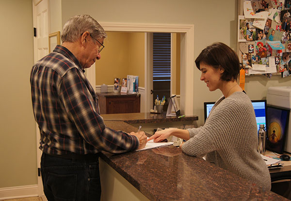 Patient welcomed at front desk of Wendy Sanger DMD Cosmetic + Family Dentistry, in Warren, NJ